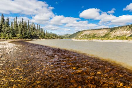 Plume of dark tea-stained creek water mixing with the glacial Nenana River water coming out of Denali Park Standard-Bild