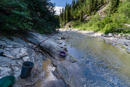 gold shovel: A prospectors tools revealed some gold in a bedrock crack in the high Alaskan mountains
