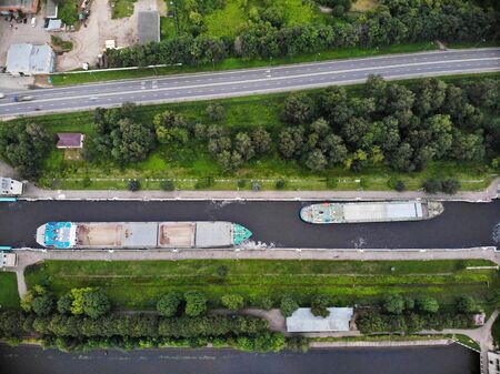 Transportation of cargo on river ships along the central river of Russia. Aerial view of chips passing through hydraulic locks on the river. Drone panorama.
