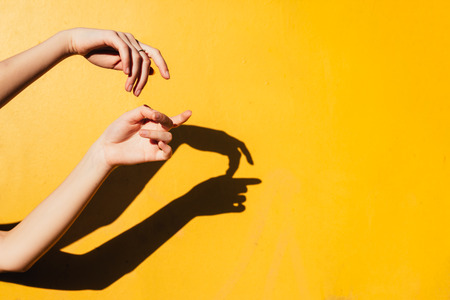 Female hand. Summer girl teen dancing under direct sun light. Art Minimal happines concept, clode up hands silhoutte with shandows on yellow background rustic
