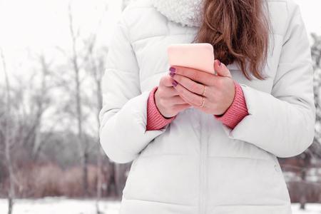 Woman using smart phone outdoors white coat pink social media blogger
