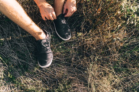 An unidentified man ties up shoelaces on black sneakers sitting in the park grass preparing to train Stock fotó