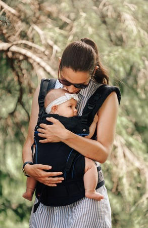 Little baby girl and her mother walking outside babywearing in the ergo carrier concept