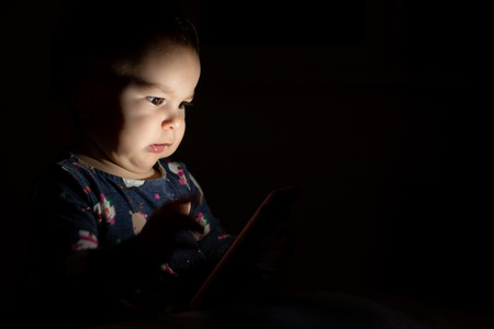 Baby toddler with face lit from phone screen at night, genration z early learning cartoons