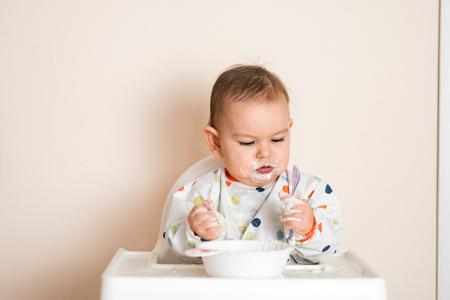 Un petit bébé mangeant son dîner et faisant un gâchis