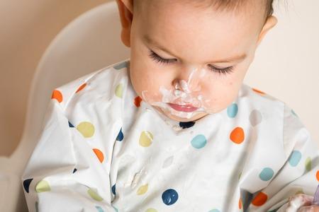 Un petit bébé mangeant son dîner et faisant un gâchis Banque d'images