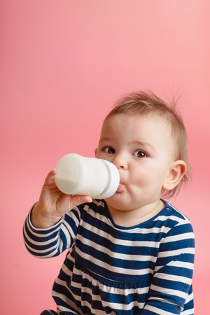 Portrait of a cute toddler drinking milk from the bottle, one year old food concept