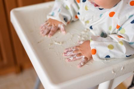 une petite fille dans un t-shirt et une assiette assise sur une chaise d'enfant mangeant avec les mains des céréales avec de la nourriture au yaourt Banque d'images