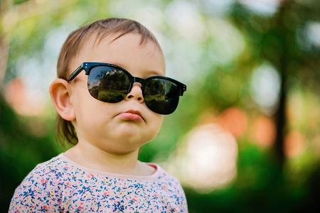 Baby mit Sonnenbrille auf grünem Grashintergrund an einem sonnigen Tag, Lifestyle