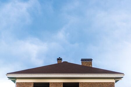 The roof of the house on blue sky background. Copy space