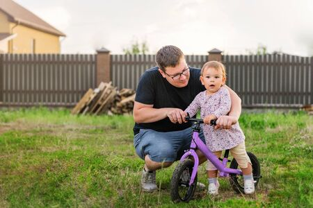 Young father spend time with Cute little one years old toddler girl child and balance bike, fathers day