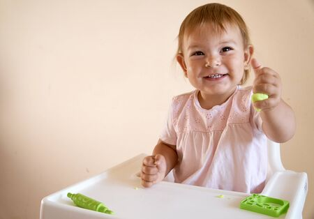 Little child engaged in playdough modeling at table, copy space. lifestyle