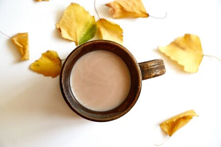 Autumn leaves with coffee or tea cup on white background. Flat lay. Copy space Stockfoto