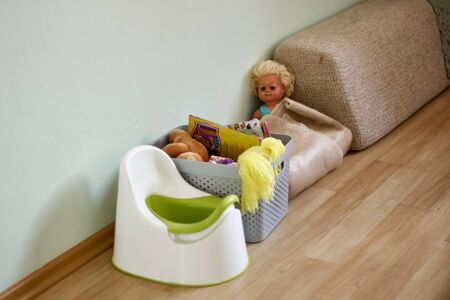 Potty and basket with toys in nursery. Training toddler. Toilet