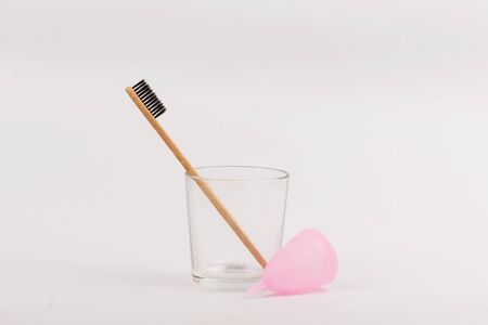 Bamboo toothbrush and menstrual cup in glass on white background. Concept zero waste Stockfoto