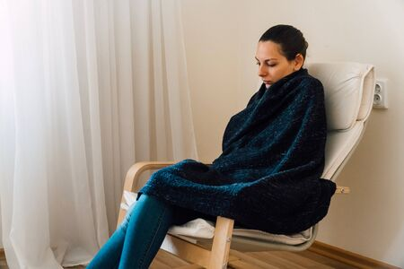 Lonely woman in armchair in blue plaid. Heating problem. Flu season. Stockfoto