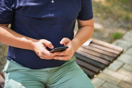 Man using smartphone on the bench in the park. Freelancer or blogger