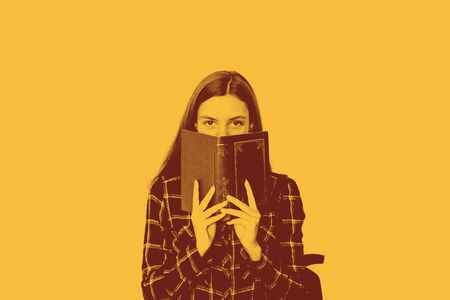 pretty teenager girl student with book in her hands hiding face with copy space Stockfoto