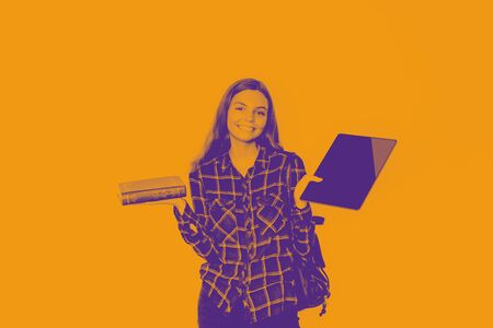 Girl holds book and tablet in her hands. BAck to school. duotone orange and blue