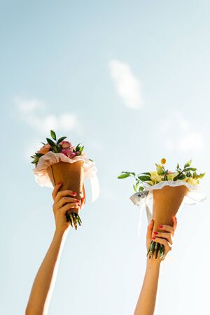 Bouquets of flowers in two hand and blue sky. Women family lgtb. Wedding day. Florist. Copy space