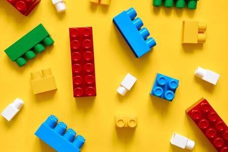 Colorful plastic building blocks flat lay. Yellow background. Child developing game. Pattern