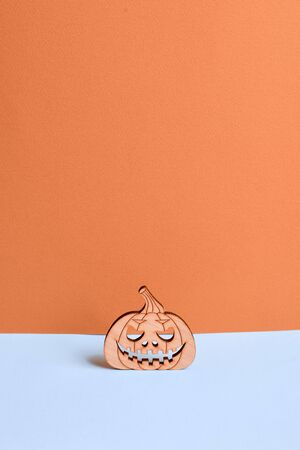 Wooden pumpkin decorative object on blue background. Halloween concept. Copy space 写真素材