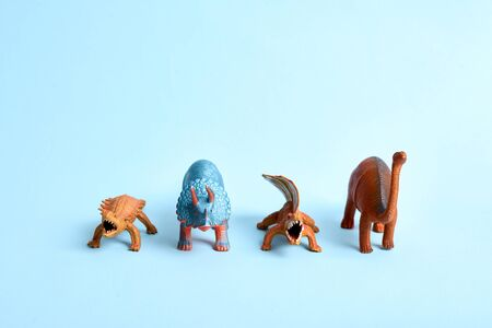 Tower of toy dinosaurus on blue background. Funny prehistoric poster. Copy space Stock Photo