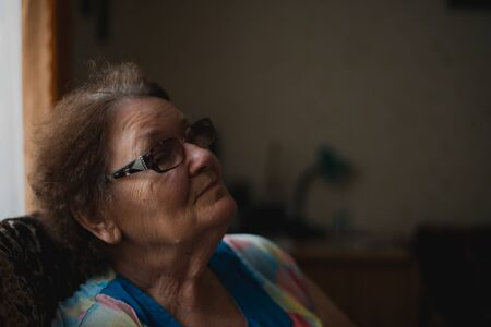 Portrait of a senior woman at home near the window. Lifestyle of retirement. Portrait in dark tones
