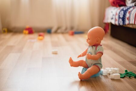 The doll sits on the potty in a playroom. Potty training toddler 写真素材 - 132198534