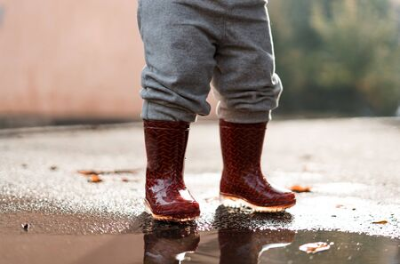 Little girl in red rainboots playing in puddle after rain. Happy fall childhood activity Stock Photo