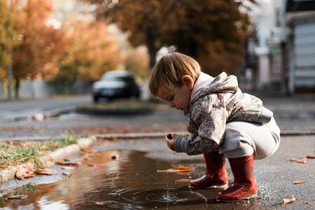 Little girl in red rainboots playing in puddle after rain. Happy fall childhood activity Stockfoto