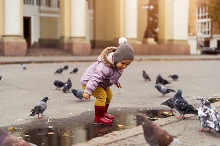 small boy playing in puddles, city square with birds. pigeons. autumn childhood