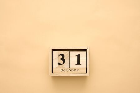 Halloween day 31 october in wooden calendar on beige background. Copy space, holiday concept