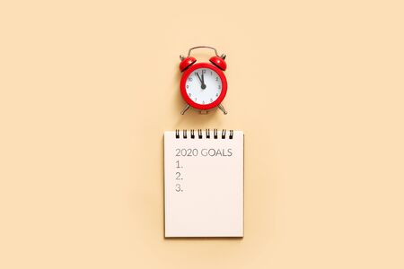 Composite image of new years resolutions against overhead of notepad and alarm clock. Beige background