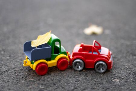 A small toy yellow truck is loaded with yellow fallen leaves. Cleaning and removal of leaves Banque d'images - 133141588