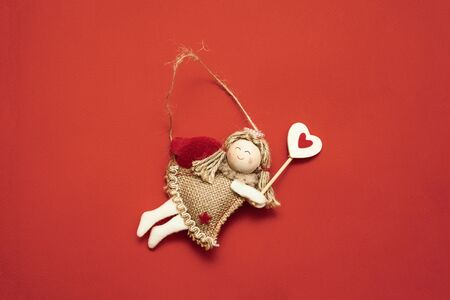 Top view of flying angel decoration on red background. Copy space Zdjęcie Seryjne