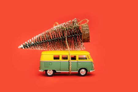 Miniature hippy car with fir tree on red background. minimal new yrar 2020