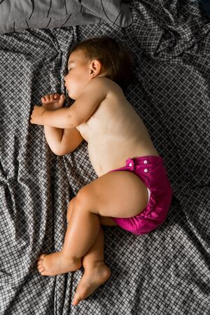 Sleeping baby with cloth diaper. Top view. Ecology reusable organic diaper. Copy space 版權商用圖片