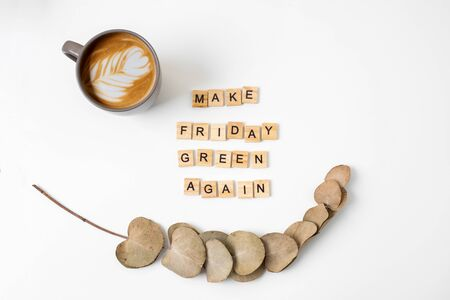 Motivating slogan Make Friday green again. Wooden letters. Top view. Coffee and eucalyptus