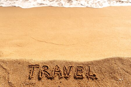 Vacation concept on the beach. Word Travel written on the sand near the sea. 版權商用圖片