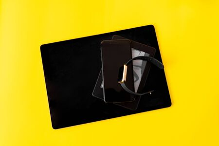 Tablet, phone, ebook, smart watch on yellow background