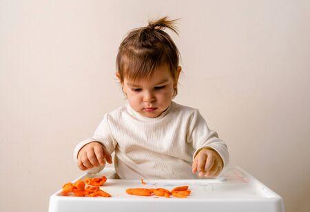 Little toddler plays play dough. Modeling orange sun. Creativity imagination