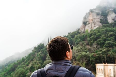 Back view of man on hiking trail. Backpacker traveling. Stock Photo