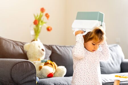 Bad behaviour toddler girl playing strange game. living room
