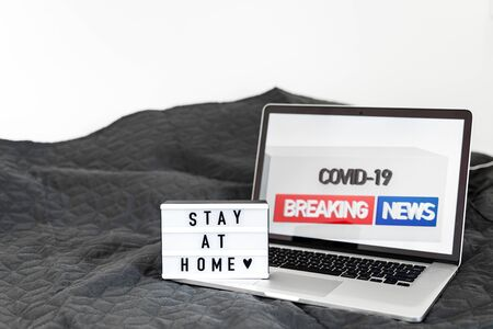 Lightbox with Stay home text on wooden background. Top view flat lay Covid-19 quote Imagens