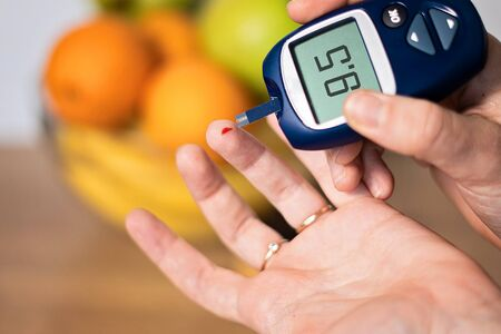 Close up of hand metering glucose in blood at home