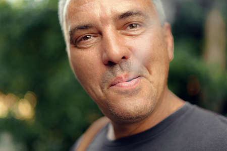 Caucasian mature middle aged man smoking cigarette outdoors. Nicotine addiction. Copy space 스톡 콘텐츠
