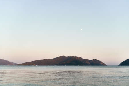 Panoramic photo of sea and hills in dusk. Traveling to nature. High quality photo
