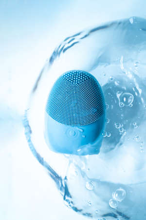 Skin massager in pure water in blue colors. Home wellness concept. Skin care