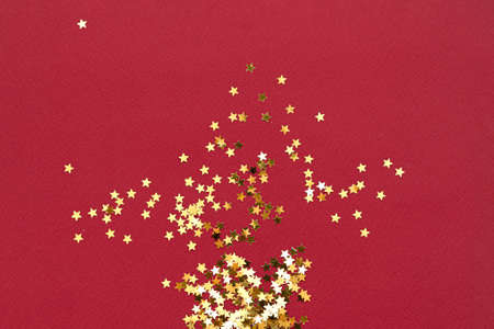 Red background with golden star glitter. Top view flat lay. Christmas background